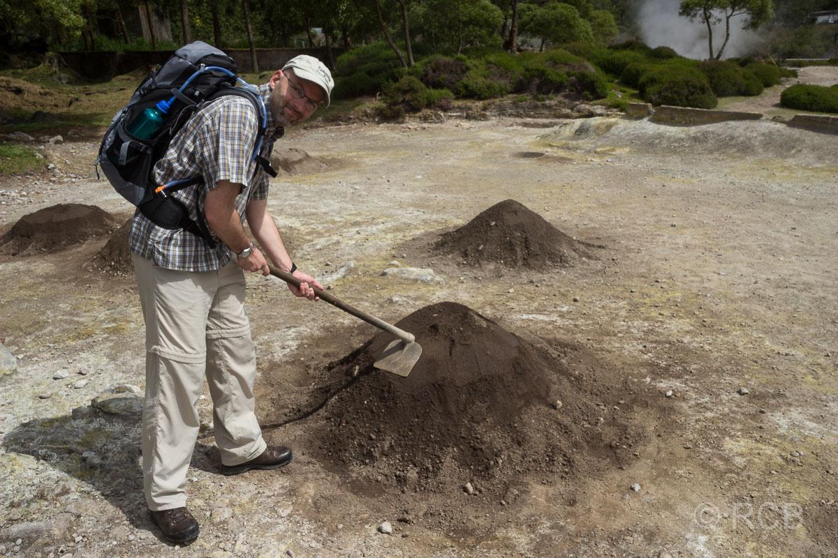 Mann demonstriert mit einer Hacke, wie die Töpfe mit dem Eintopf Cozido in der Erde vergraben werden.