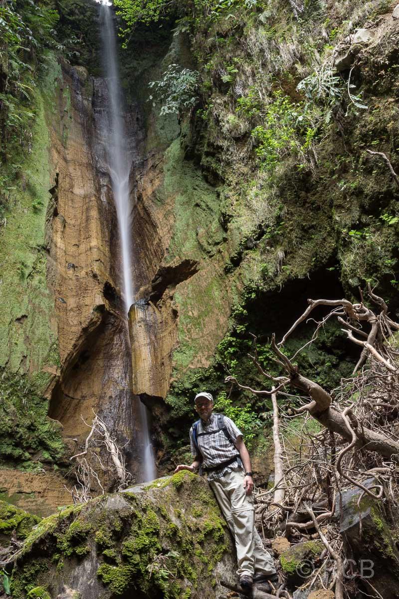 Mann unter dem Wasserfall Ribeira do Rosal