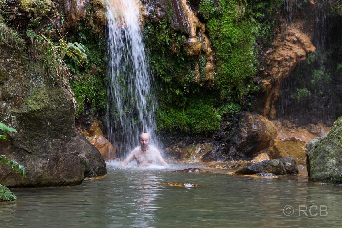 Mann badet unter einem Wasserfall an der Caldera Velha