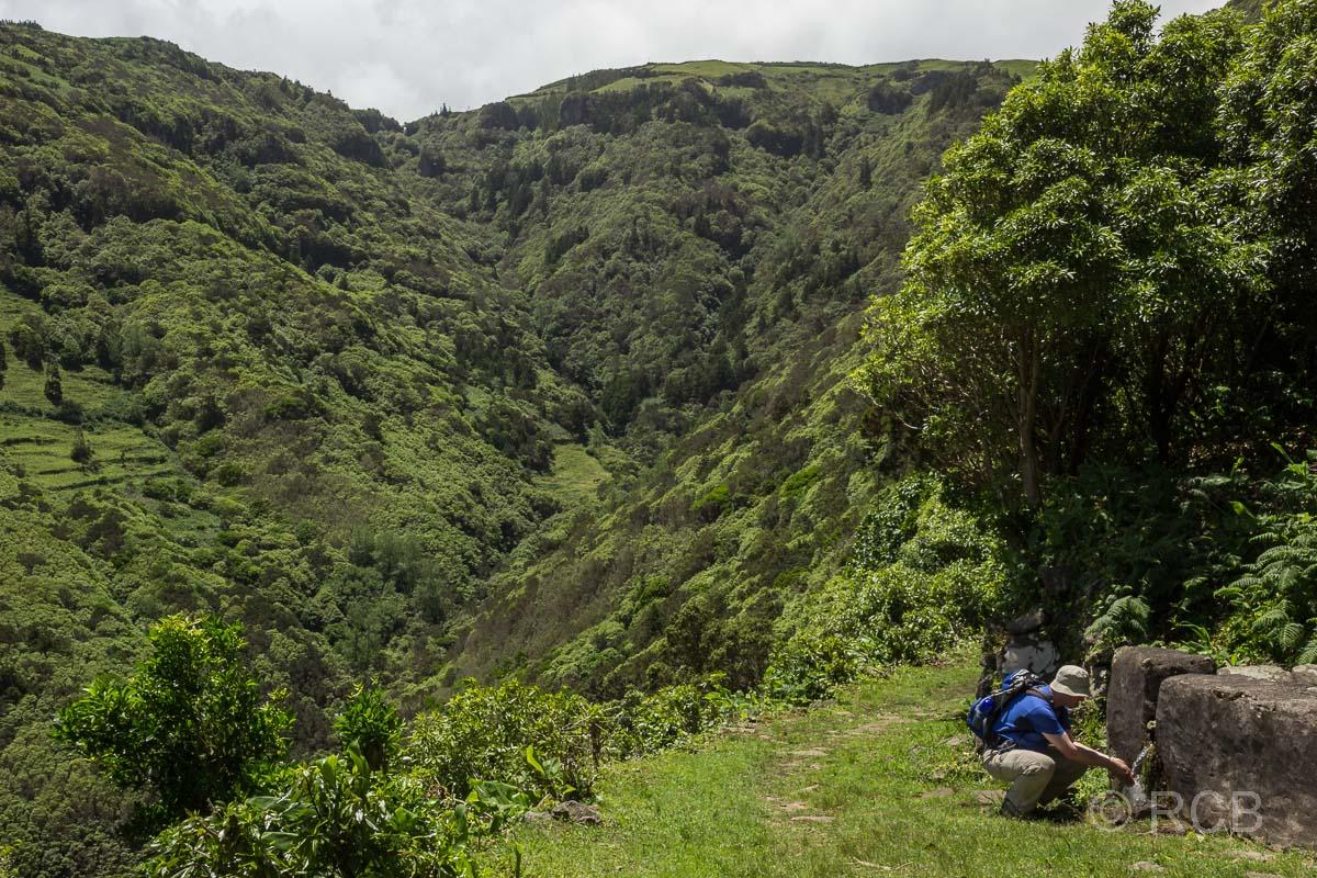 Mann schöpft Wasser an einem Brunnen auf einer Wanderung von Cedros nach Ponta Ruiva