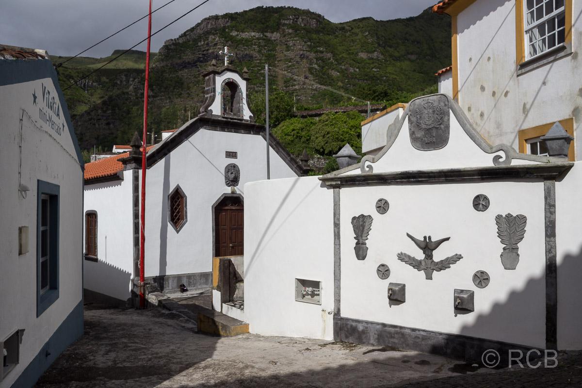 Straßenzug mit schwarzweißen Häusern in Fajã Grande