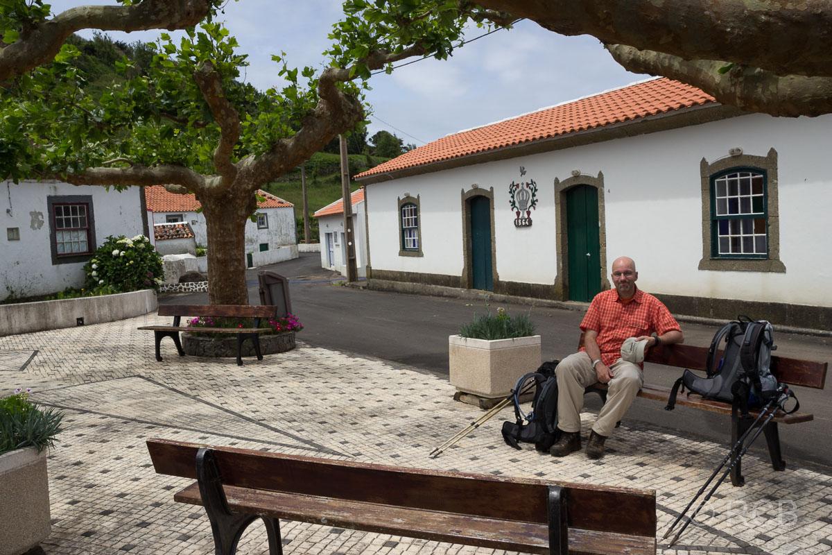 Mann rastet auf einer Bank auf dem Dorfplatz von Fajãzinha