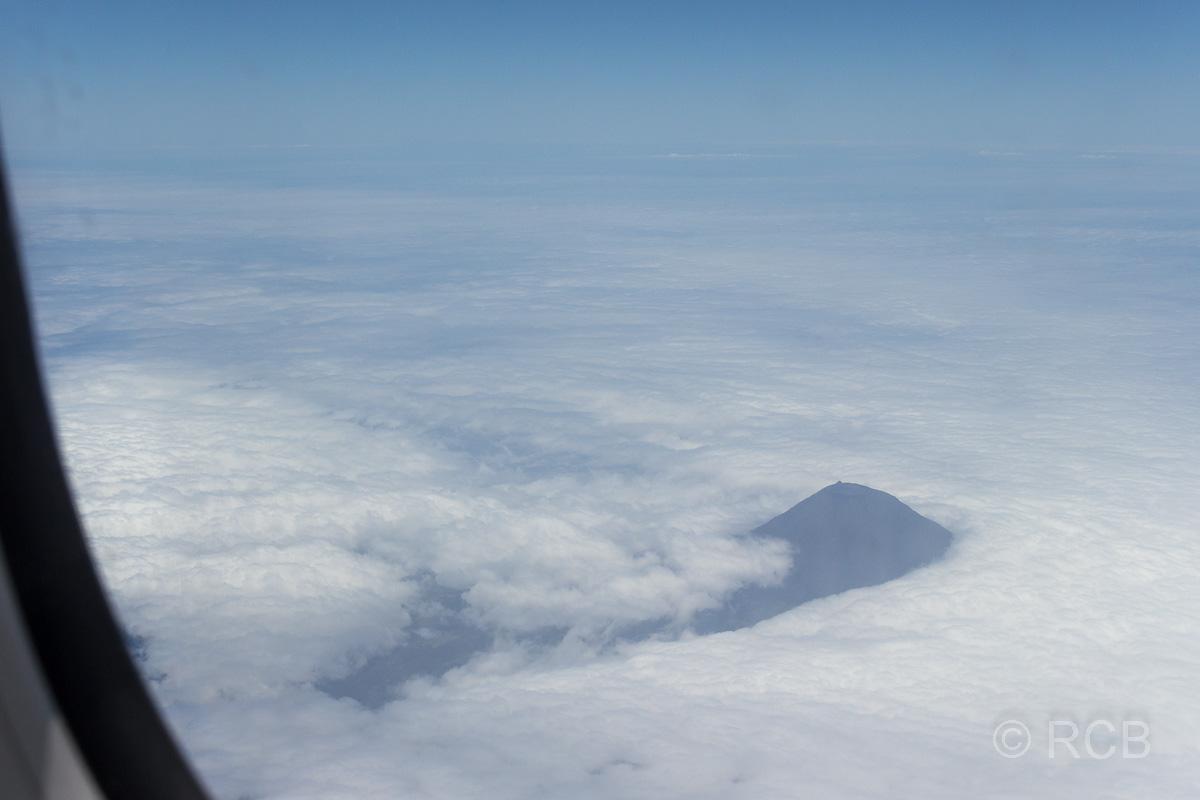 Blick aus dem Flugzeug auf den Gipfel des Pico, der aus den Wolken ragt.