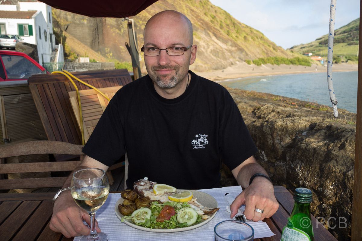 Horta, Mann beim Abendessen am alten Hafenbecken Porto Pim