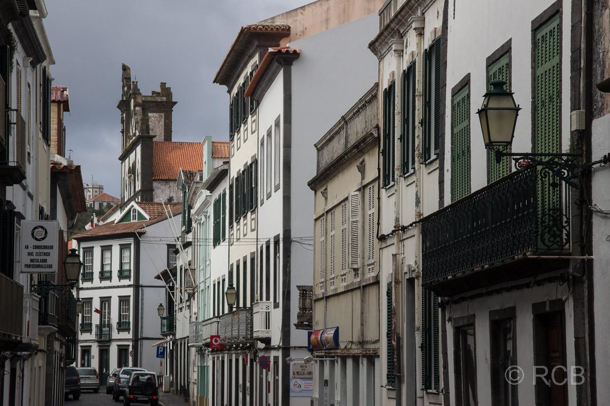 Horta, Häuserfassaden mit Kirche im Hintergrund