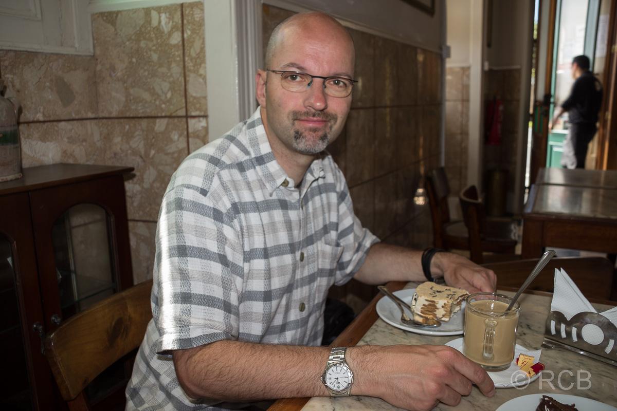 """Horta, Mann isst Kuchen im """"Café International"""""""