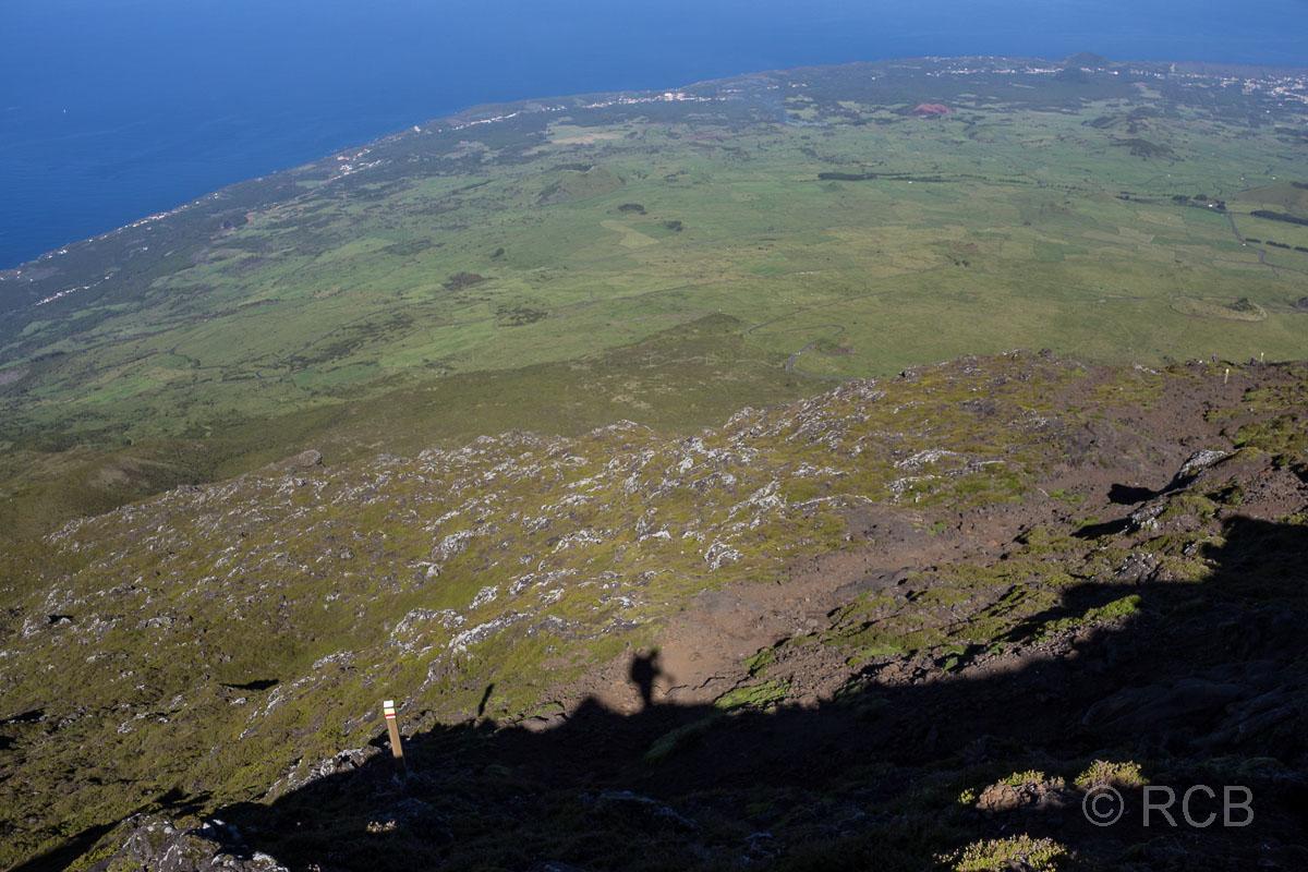 Schatten eines Wanderers am Hang des Pico mit Blick auf den Ort Madalena