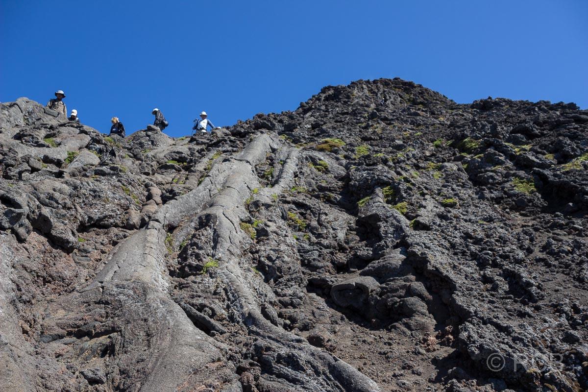 Menschen kommen einen steilen, von erstarrter Lava überzogenen Hang hinab vom Pico Pequenho