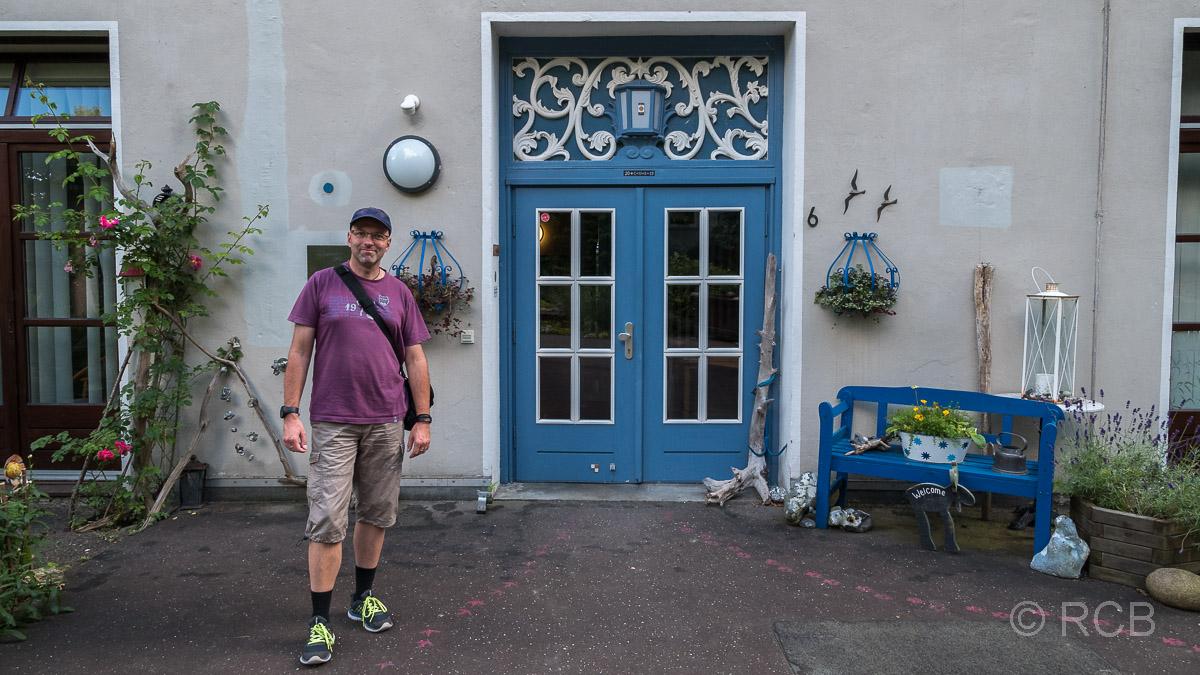 """Mann vor dem Ferienhaus """"Holsteinische Schweiz"""""""