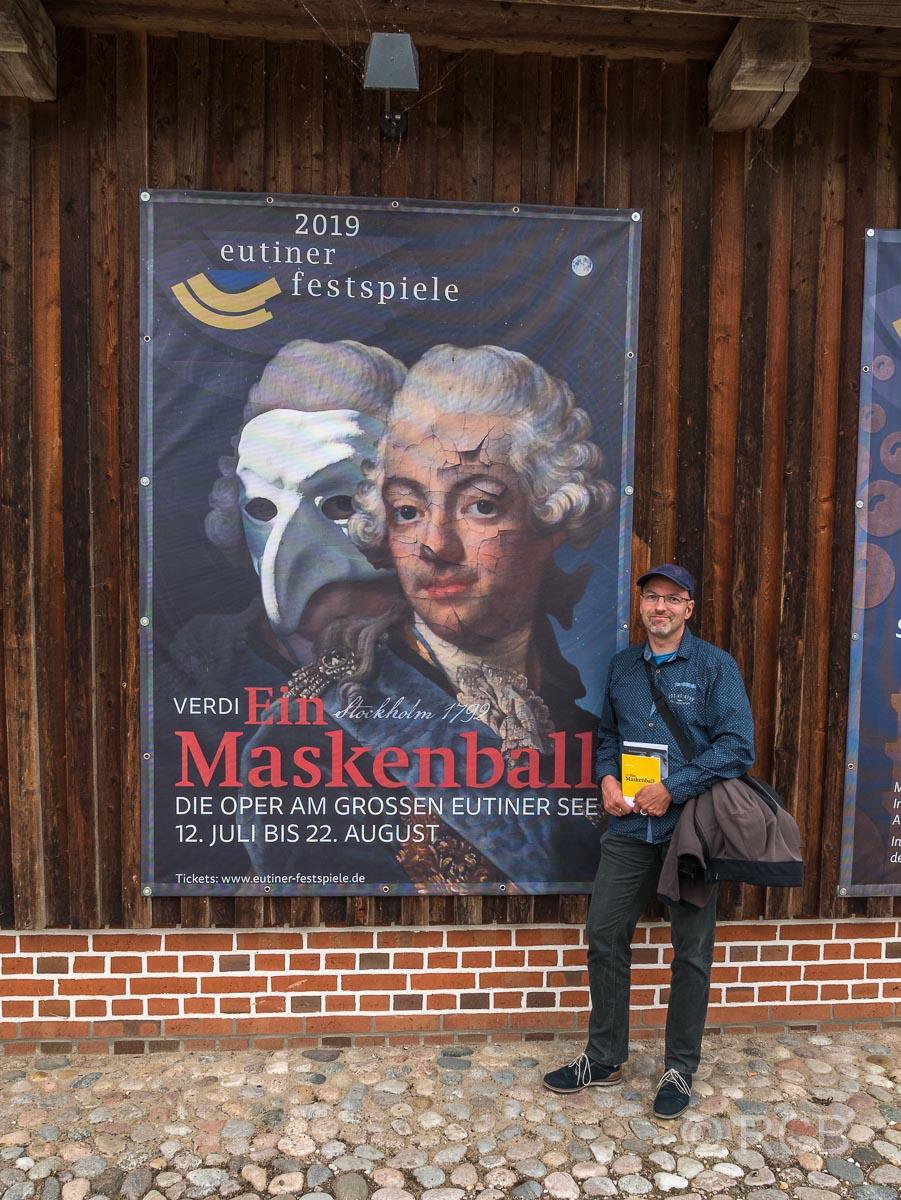 """Mann vor Plakat der Eutiner Festspiele mit Verdis """"Maskenball"""""""