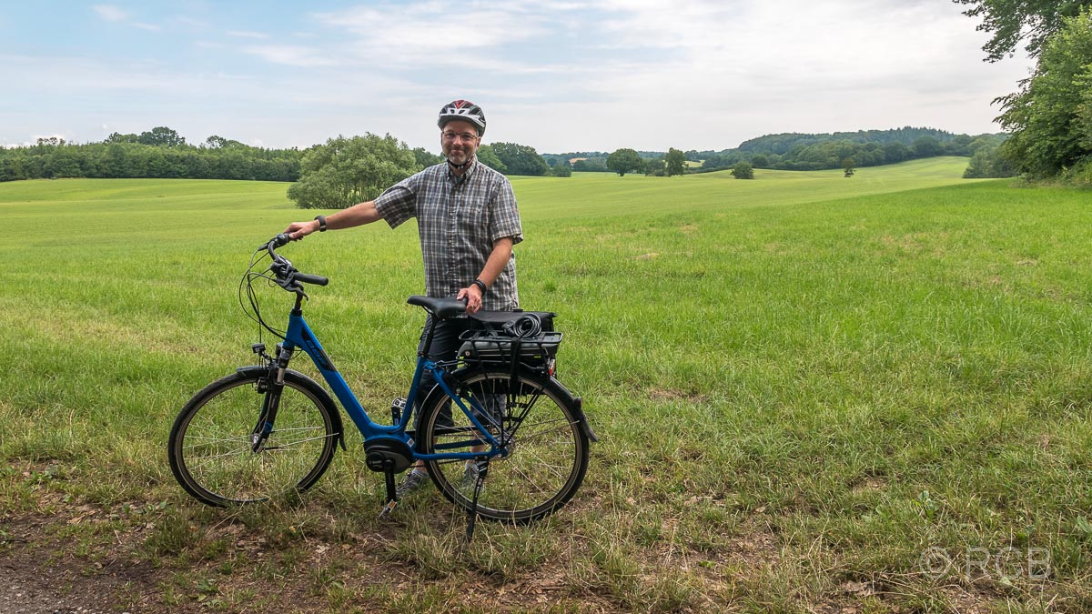 Mann mit E-Bike vor einer Wiese