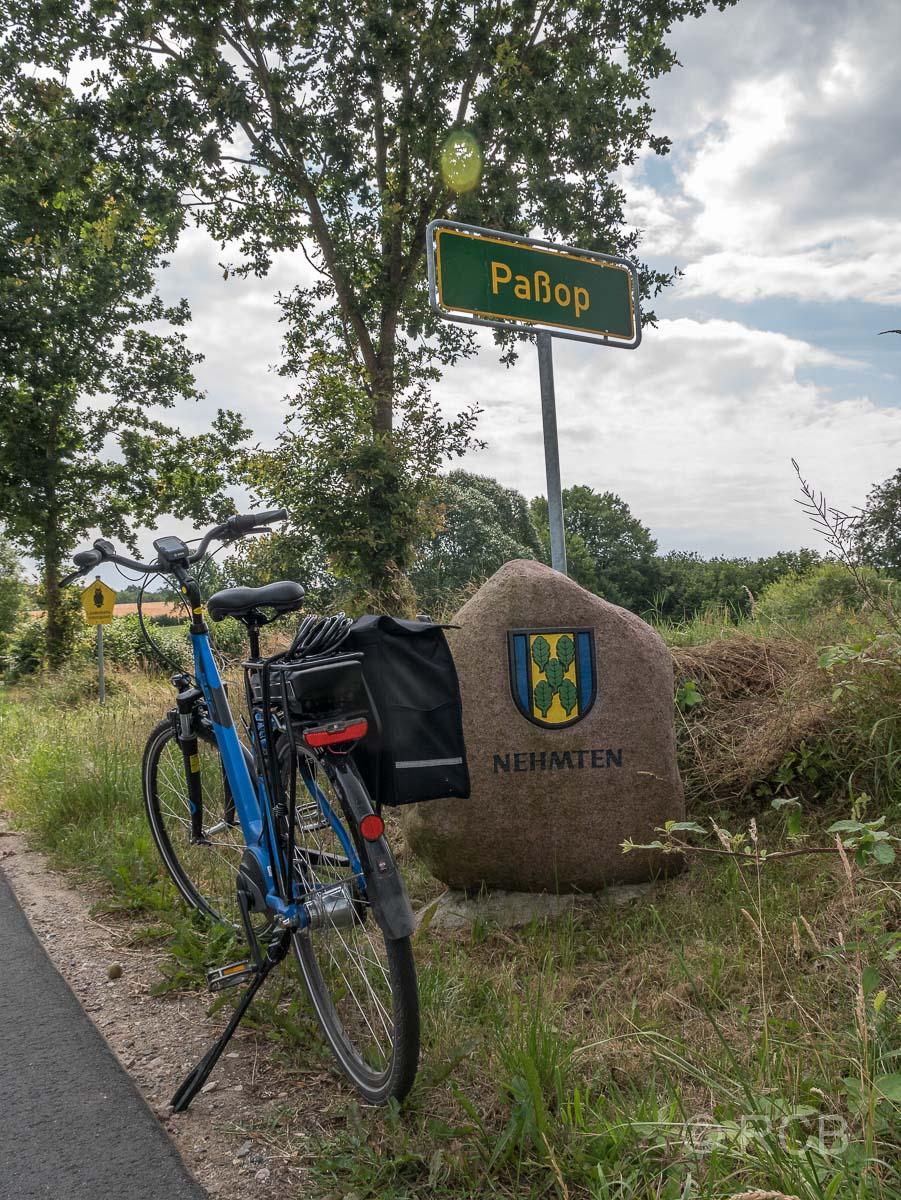 """Fahrrad vor dem Ortsschild mit dem Namen """"Paßop"""""""