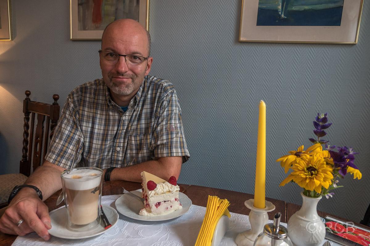 Mann vor einem Stück Kuchen in Brooks Café Achter de Mur in Bosau