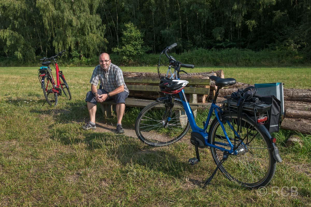 Radfahrer macht Pause auf einer Bank am Dieksee