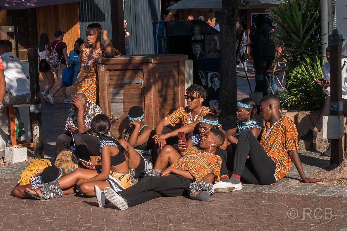 junge Musiker und Tänzer ruhen sich nach einem Auftritt aus an der V&A Waterfront