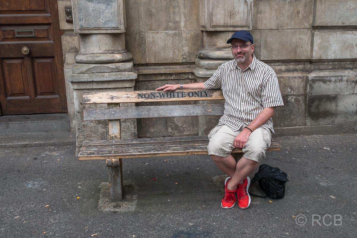 """weißer Mann sitzt auf einer Bank aus der Zeit aus der Apartheid mit der Aufschrift """"Nur für Nicht-Weiße"""""""