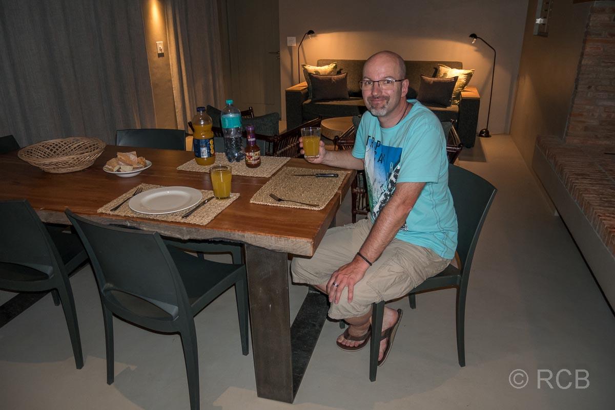 Mann sitzt am Esstisch in einem Ferienhaus in Kromrivier