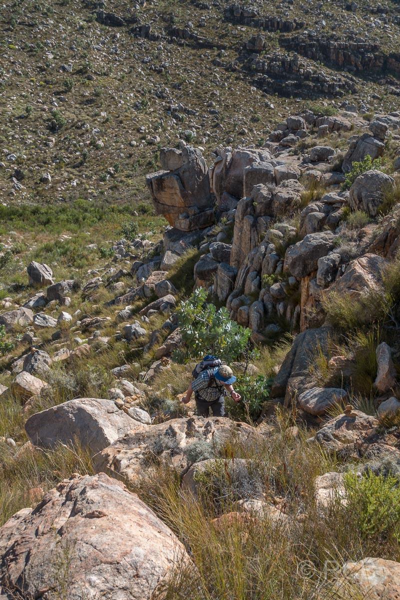Mann erklimmt einen Berg beim Ausstieg aus dem Tal des Kromrivier