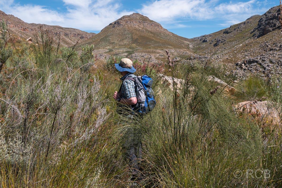 Mann auf einem Wanderweg oberhalb des Tals des Kromrivier