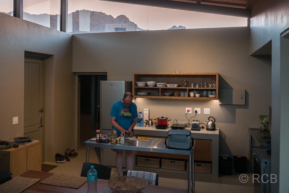 Mann in der Küche eines Ferienhauses, Kromrivier
