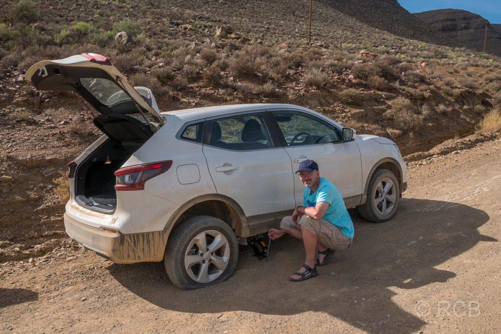 Mann behebt eine Reifenpanne in den Cederbergen