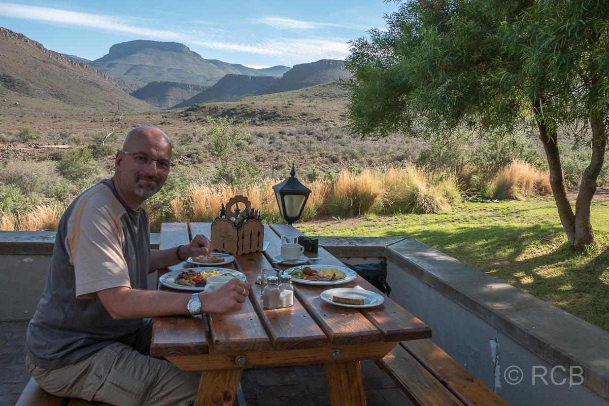 Mann beim Frühstück auf einer Terrasse im Karoo NP