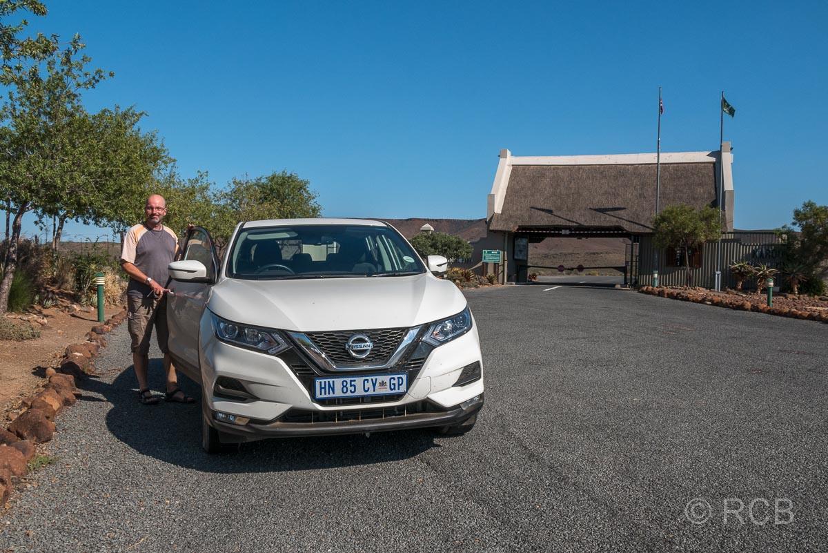 Mann vor Auto am Pförtnerhäuschen des Karoo National Park
