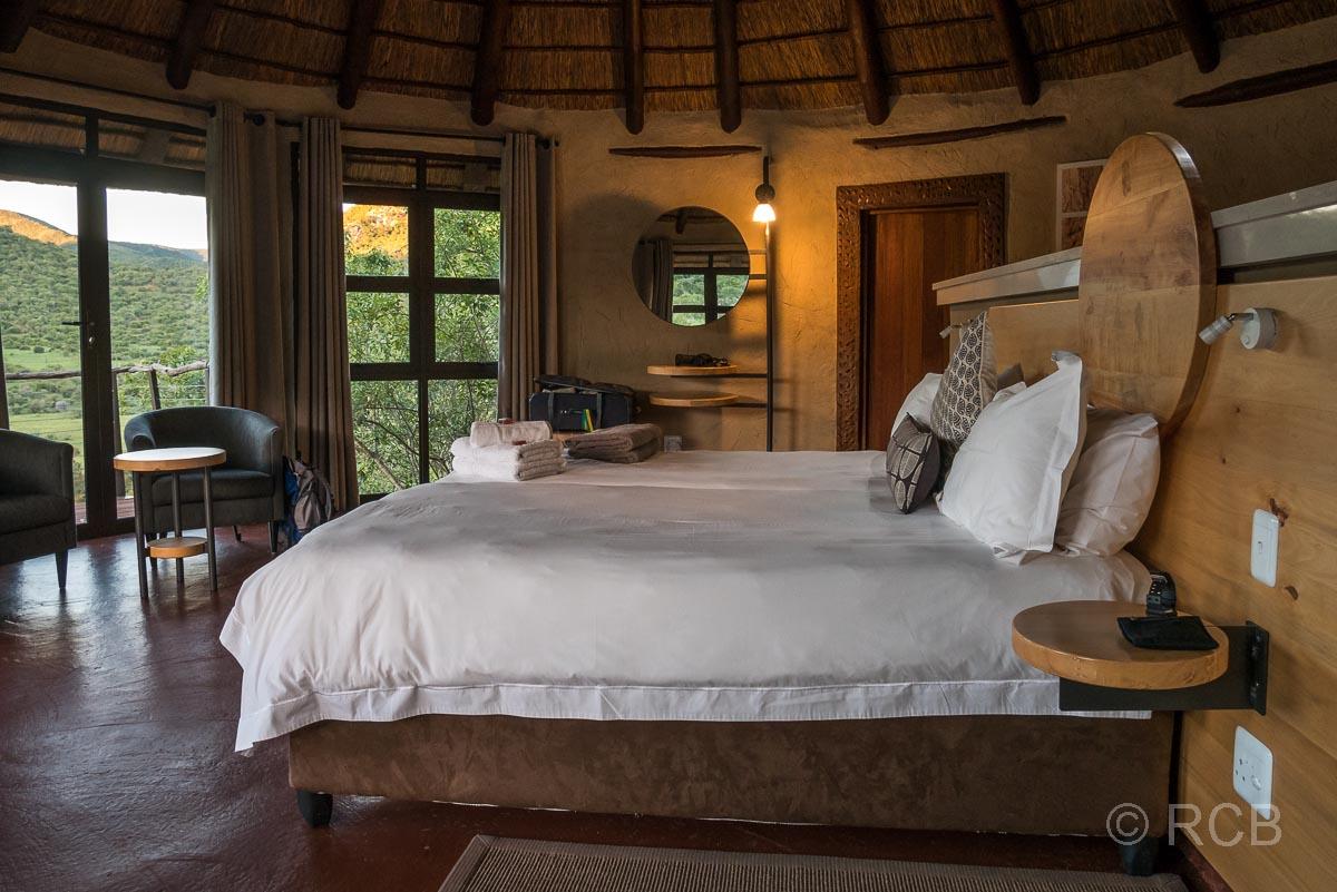 Bett in einer Lodge mit Blick über die grüne Landschaft, Addo Elephant National Park