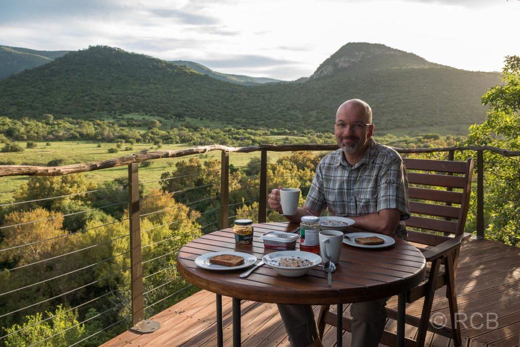 Mann frühstückt auf der Terrasse einer Lodge im Addo Elephant National Park mit weitem Blick über die Landschaft