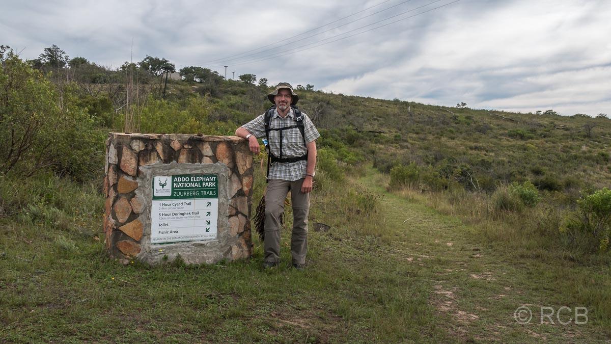 Mann lehnt an einem Schild, das den Beginn eines Wanderwegs im Addo Elephant National Park markiert