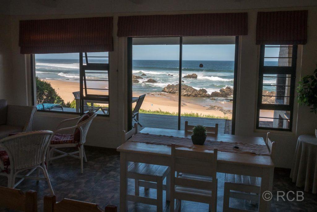 Inneres eines Ferienhauses mit Blick durch das Fenster auf Strand und Meeresbrandung