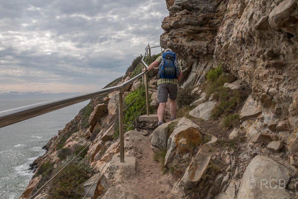Mann erklettert einen gesicherten Wanderpfad auf der Robberg Peninsula