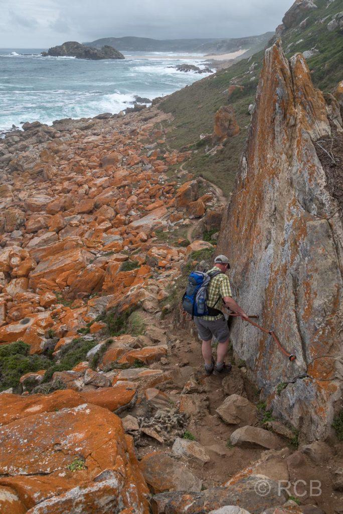 Mann hangelt sich an einem Seil entlang auf dem Rundwanderweg um die Robberg Peninsula