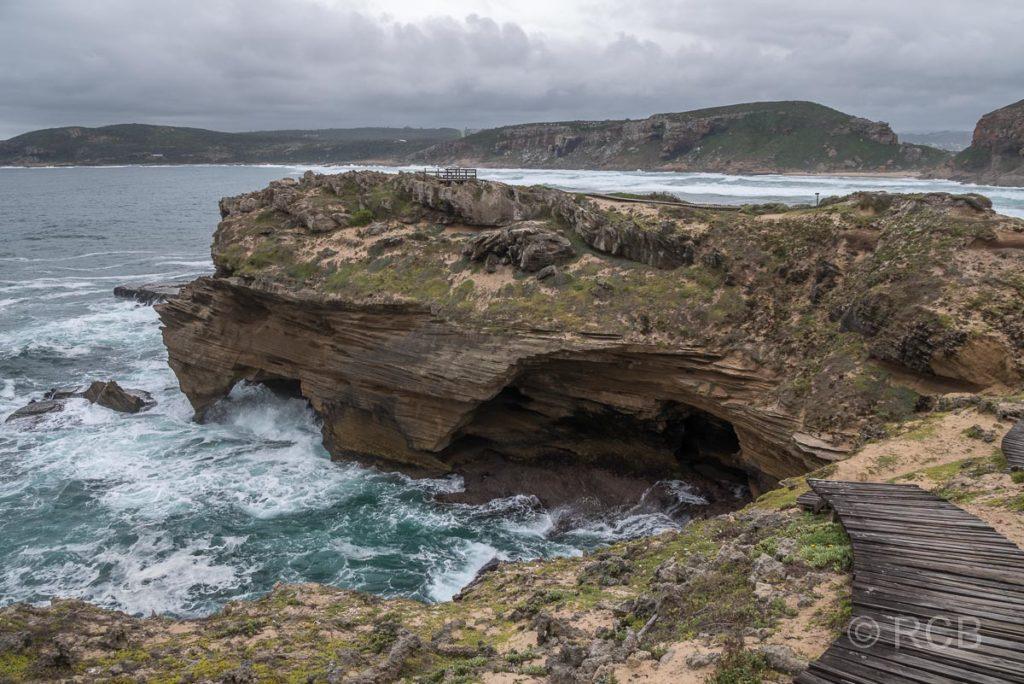 Wanderweg mit Blick zu einer Meeresgrotte auf Die Eiland, einer der Robberg Peninsula vorgelagerten Halbinsel