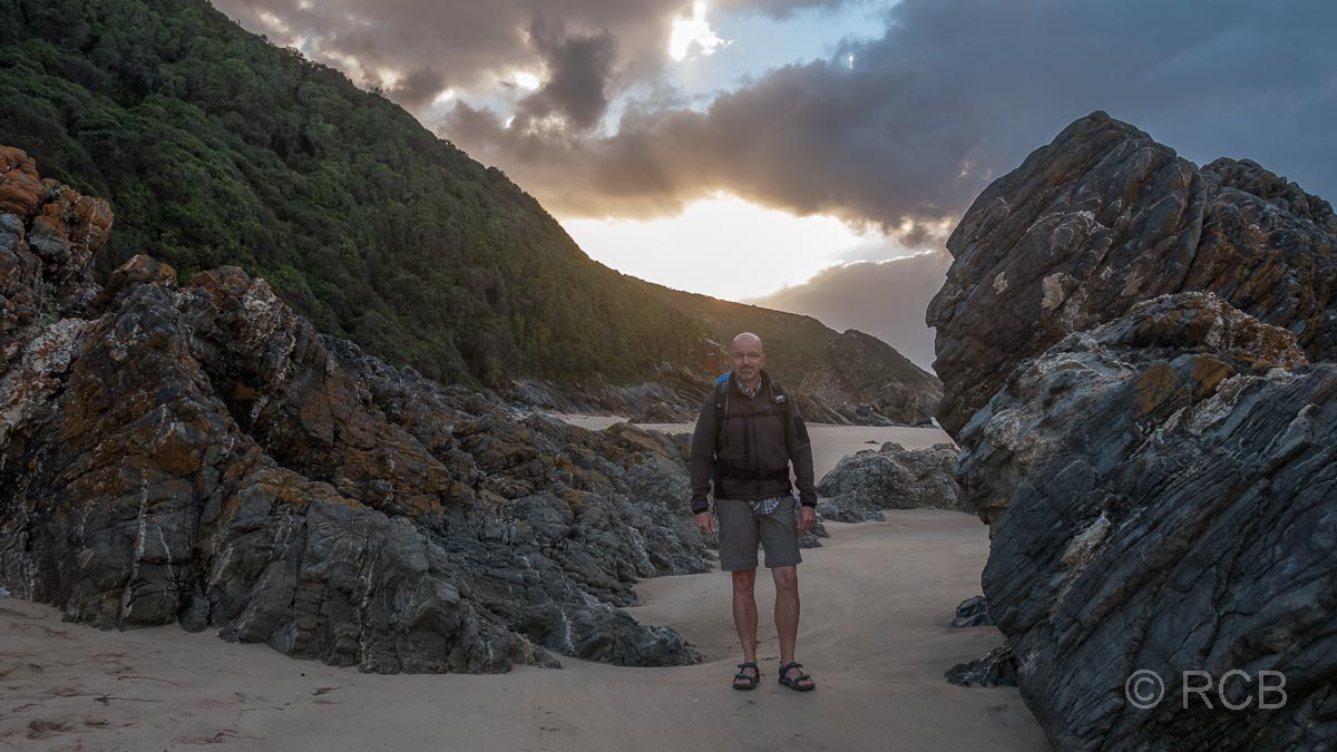 Mann zwischen Felsen bei Keurboomstrand zu Sonnenaufgang