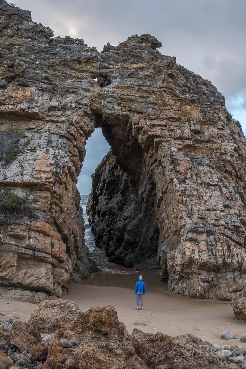 Winzig wirkender Mann unter dem großen Felsbogen des Arch Rock bei Keurboomstrand