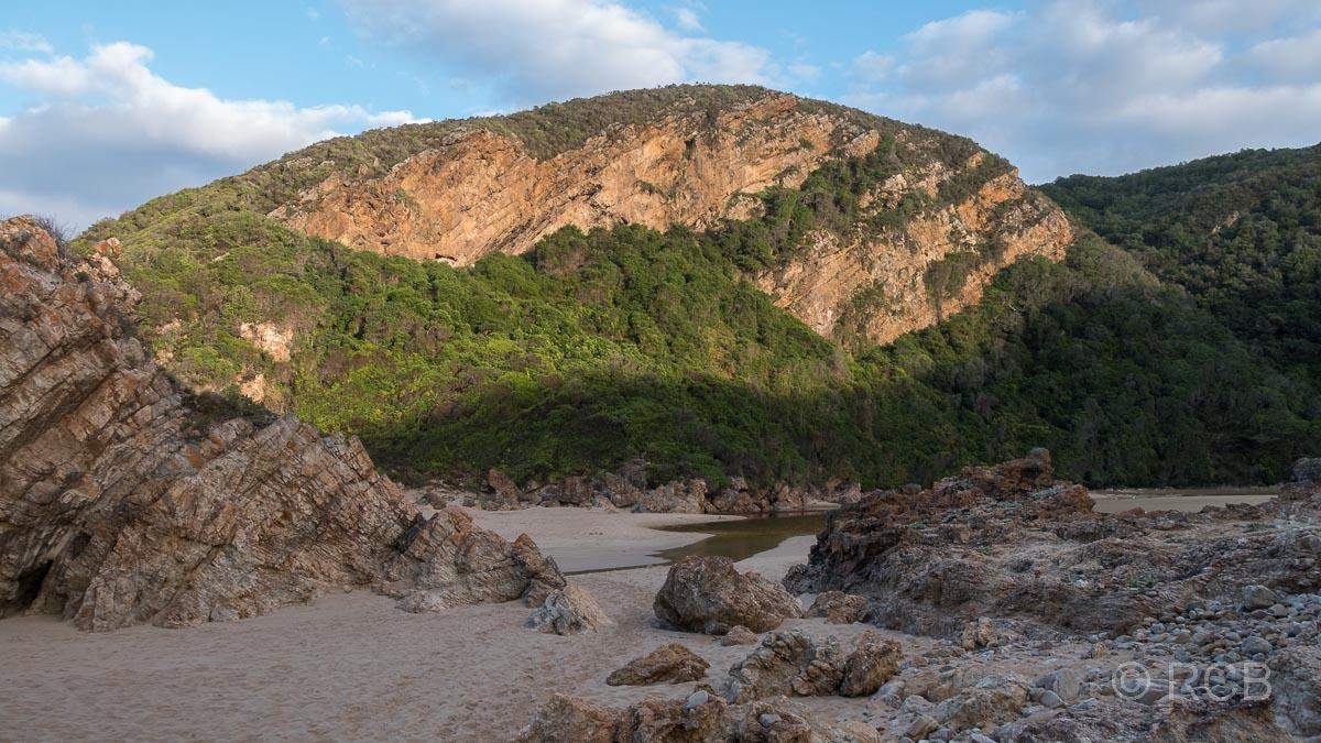 Die aufgehende Sonne bestrahlt Felsen bei Keurboomstrand