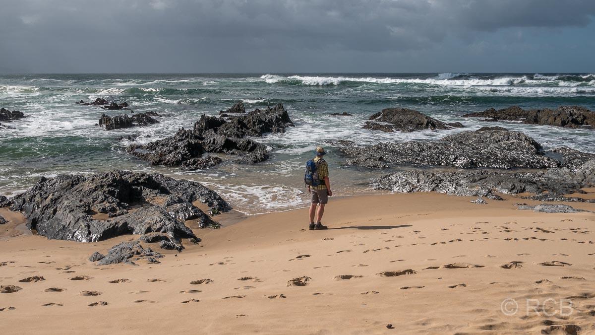 Mann betrachtet die Wellen am Strand von Nature's Valley