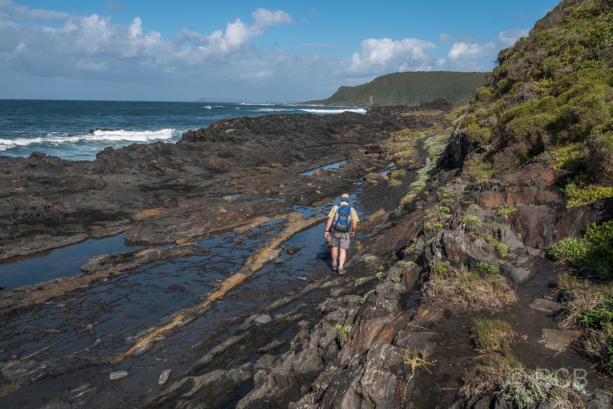 Mann wandert über Felsen auf dem Salt River Mouth Trail bei Nature's Valley