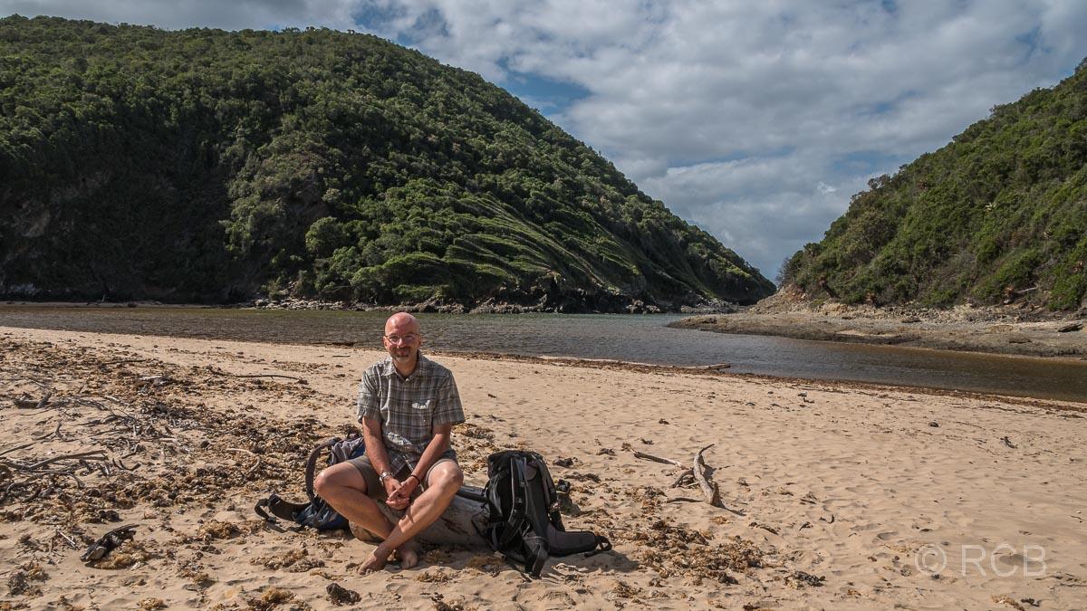 Mann sitzt barfuß am sandigen Ufer des Salt River Mouth bei Nature's Valley