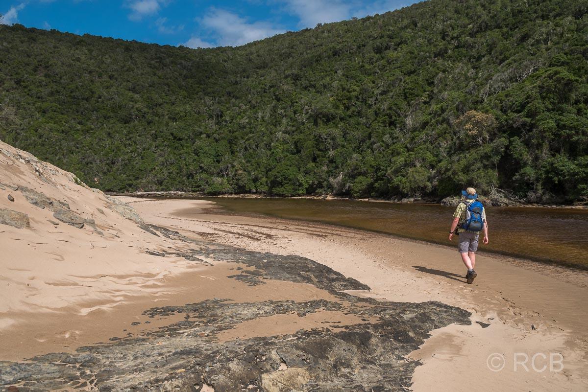 Mann wandert entlang des sandigen Ufers am Salt River Mouth bei Nature's Valley