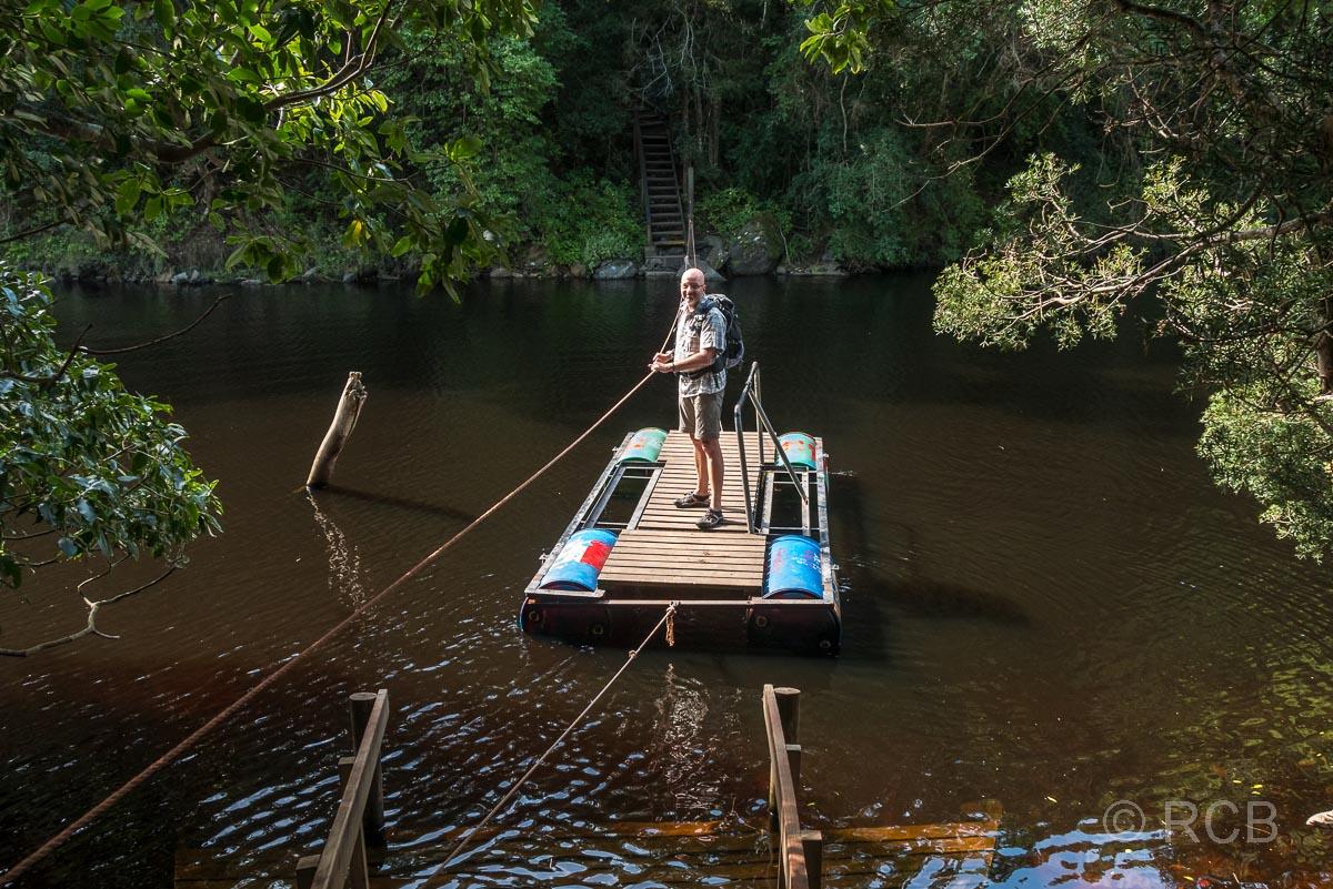 Mann zieht sich mit einer Fußgänger-Pontonfähre über den Touws River bei Wilderness