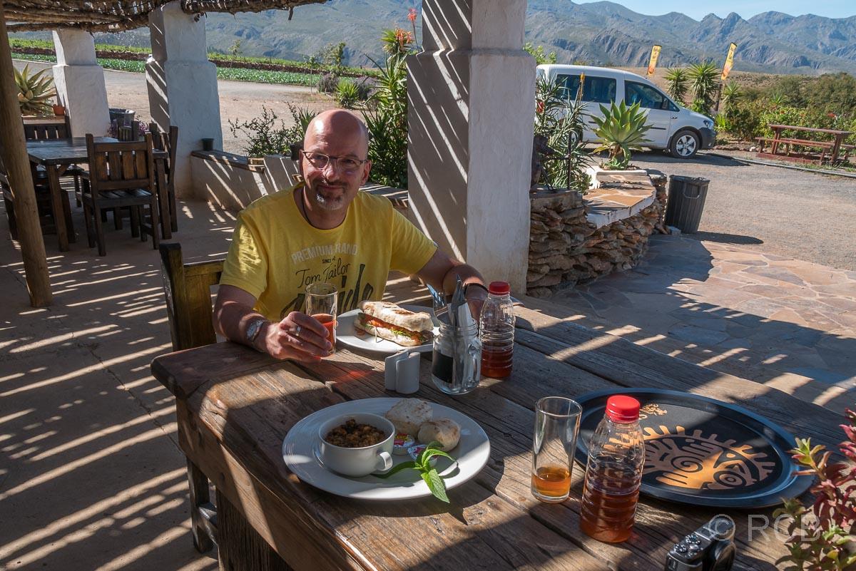 """Mann vor seinem Essen im Lokal """"Kobus Se Gat"""" am Swartberg Pass"""