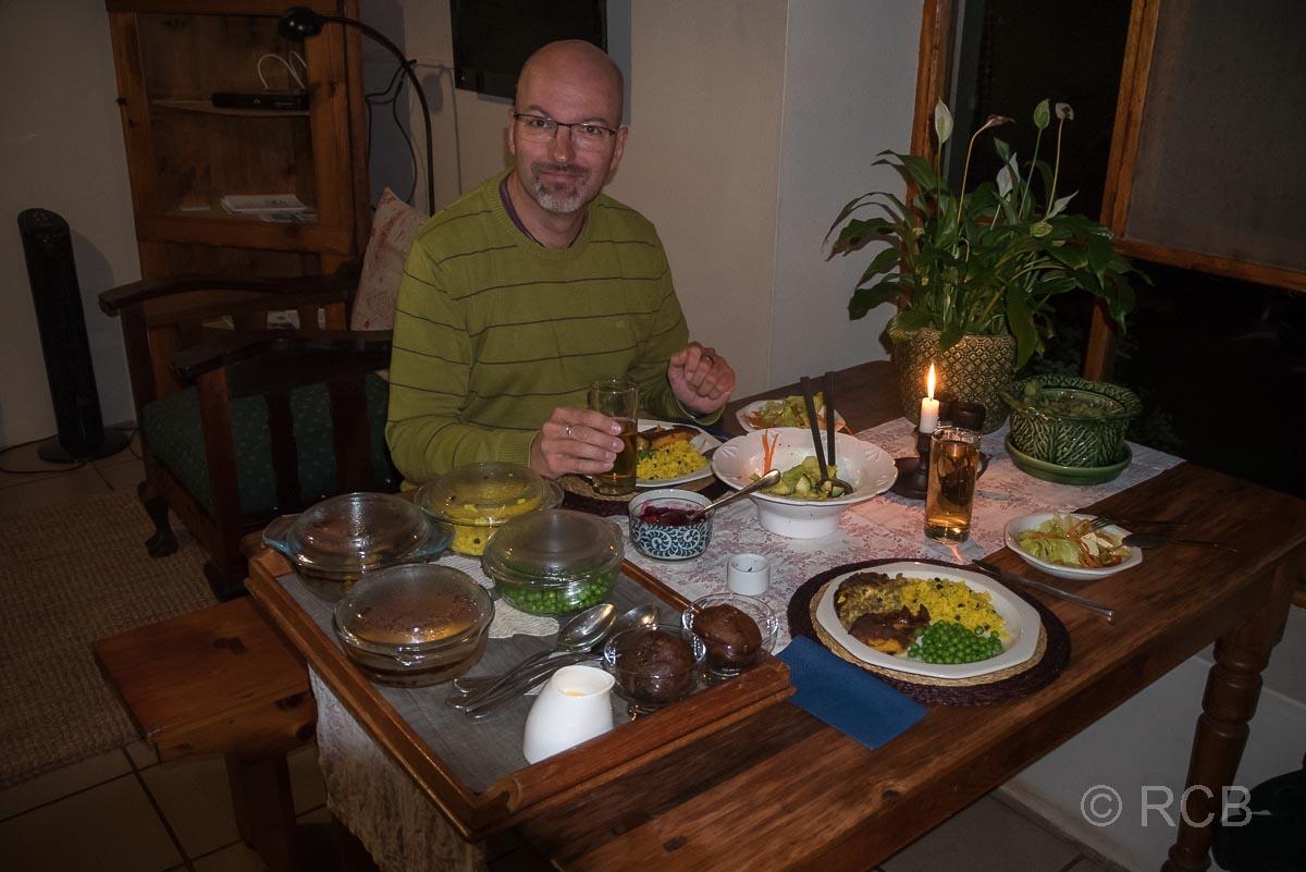Mann beim Abendessen mit der südafrikanischen Spezialität Bobotie, Potteberg Guest Farm