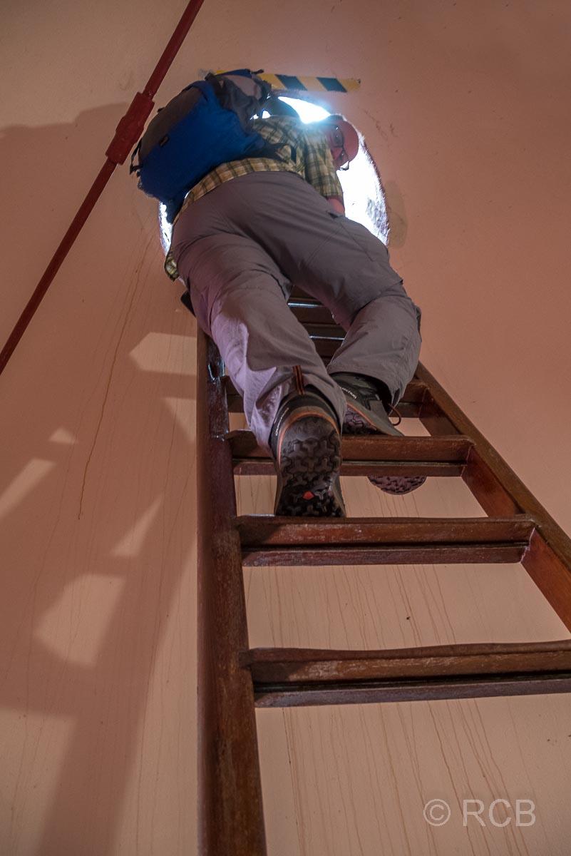 Mann klettert auf einer Leiter hoch im Leuchtturm am Cape Agulhas