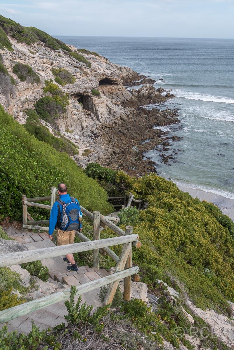 Mann geht eine Treppe hinab zur Klipgat Cave