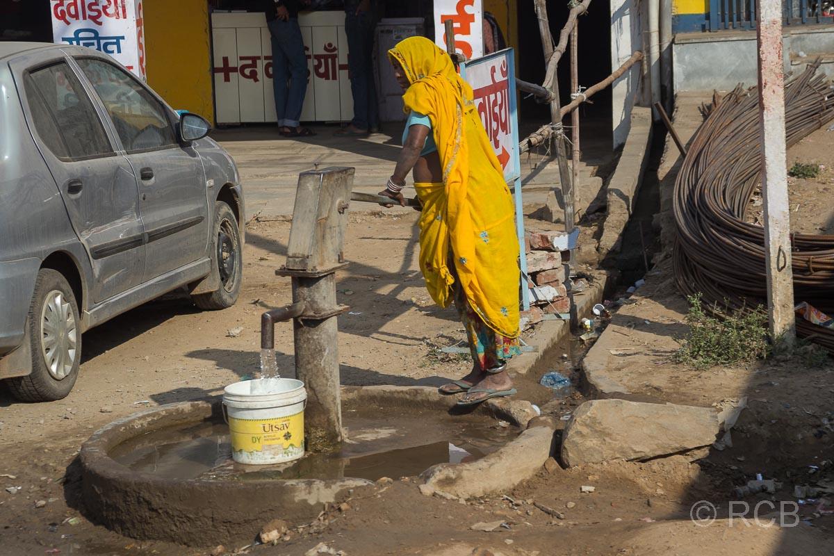 Frau pumpt Wasser an einem Brunnen in Rajasthan