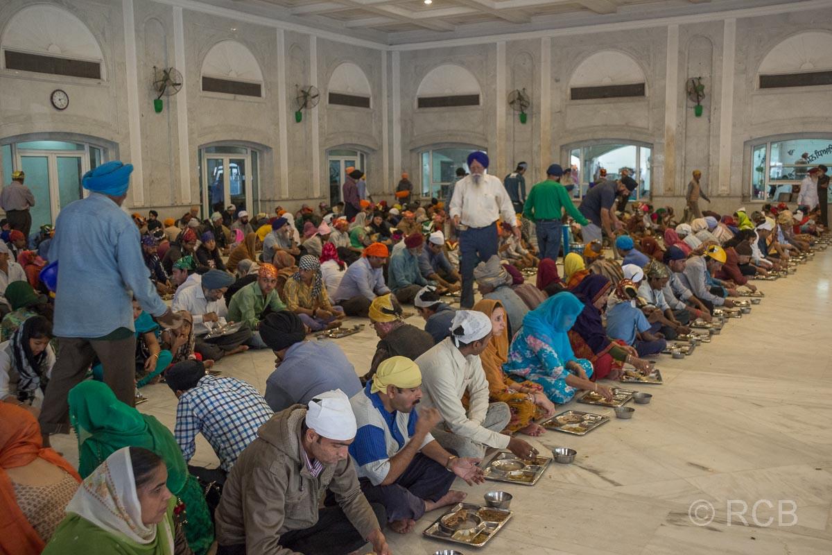 Menschen essen in langen Reihen bei der Speisung im Sikh-Tempel Bangla Sahib Gurudwara, Delhi