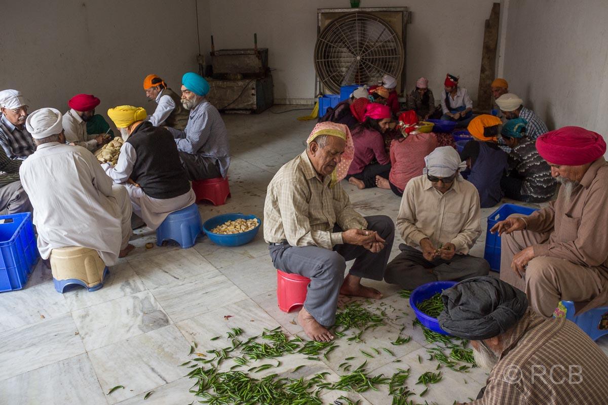 Menschen schneiden Gemüse als Vorbereitungen für die Speisung im Sikh-Tempel Bangla Sahib Gurudwara, Delhi