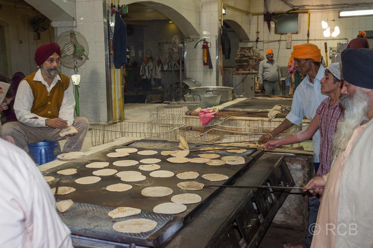 Männer backen Fladenbrote bei den Vorbereitungen für die Speisung im Sikh-Tempel Bangla Sahib Gurudwara, Delhi